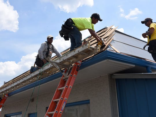 A roofing crew deals with the 90-degree temperature