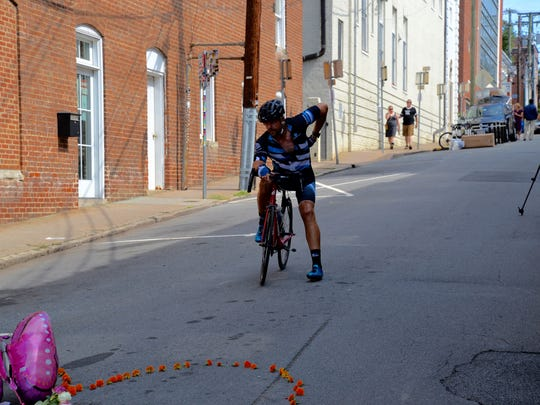 A cyclist pays his respects at the intersection of Fourth and Water streets in downtown Charlottesville on Sunday, Aug. 13, 2017. The day prior, a group of protesters was struck by a vehicle leaving on woman, Heather Heyer of Charlottesville, dead.