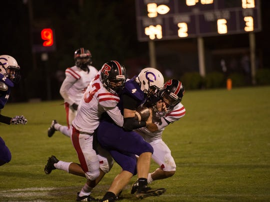 Two Rossview players go to tackle Ford Cooper of Clarksville