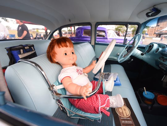 A baby doll has it's own steering wheels in this 1957