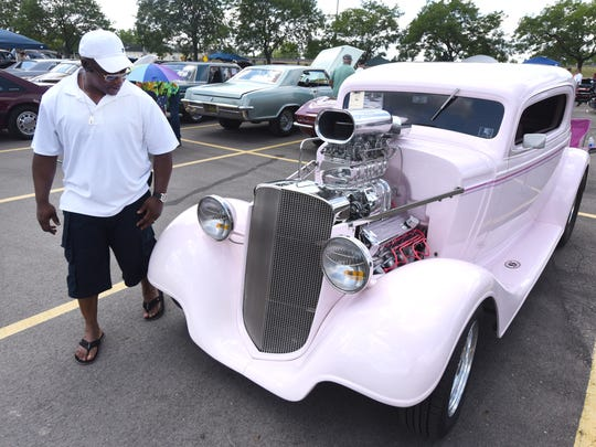 Dwayne Green of Pontiac looks at an audaciously pink 1934 Chevy Coupe with plenty of horsepower on Pike Street for the Woodward Dream Cruise on Saturday August 19, 2017 in Pontiac.