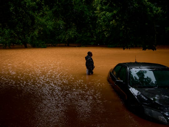 Willie Dunlap stands in his backyard next to his submerged