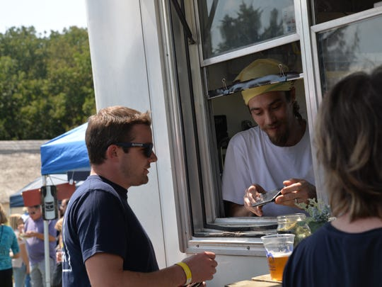 Carter Raab of Farm Fresh Fixins helps a customer at the third annual Virginia Food Truck Battle at the Frontier Culture Museum on Sunday, Sept. 3, 2017.
