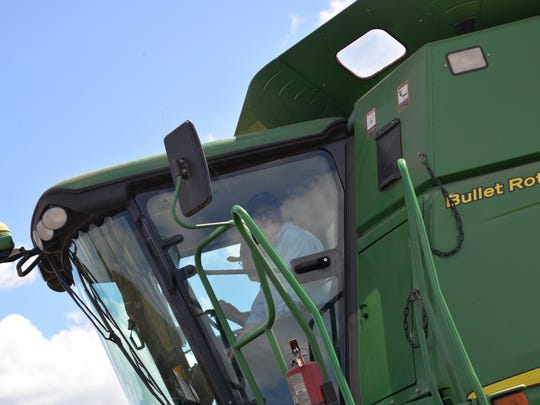 U.S. Rep. Bob Goodlate rides on a combine that is harvesting