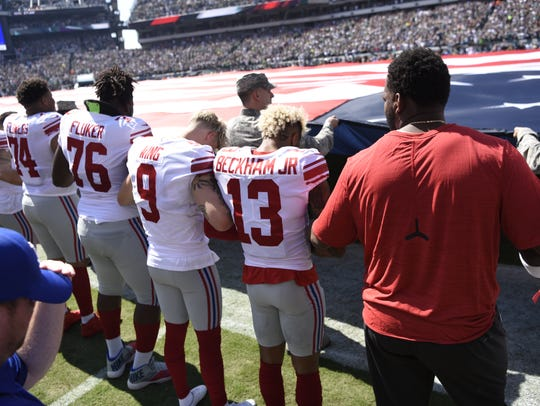 The New York Giants stand arm-in-arm during the National