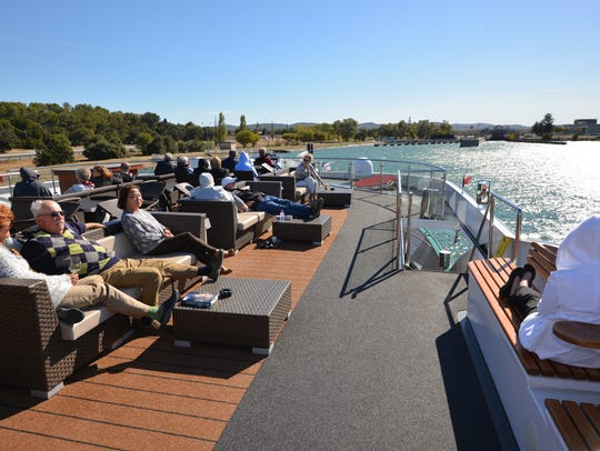 Emerald passengers look out over the Rhone River from