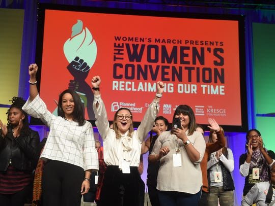 Breanne Butter (center), of Detroit, raises her fist