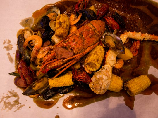 A seafood combo at Storming Crab in Clarksville, including a full lobster, shrimp, corn, and a crab leg.