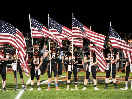 Hanover football team members hold American flags in honor of Jeremy Redding, a Hanover graduate who served in the United States Marine Corps and passed away in 2010.