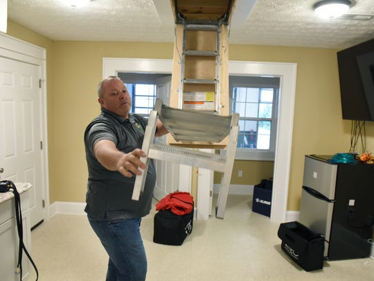Jason Estes shows off a small model house demonstrating weatherization techniques Wednesday, Nov. 8, 2017. The house is used to do community demonstrations.