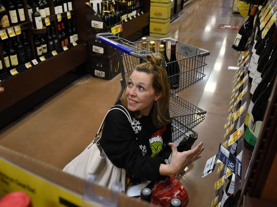Megan Collins shopping for holiday wine at the Cedar Bluff Kroger Marketplace Thursday, Dec. 21, 2017. Kevin Valley, out of frame left, is the wine steward for the store and offers help to shopping customer.