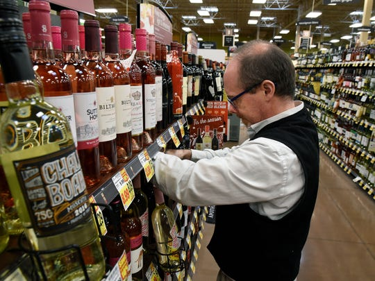 Kevin Valley, wine steward at the Cedar Bluff Kroger Marketplace, straightens stock Thursday, Dec. 21, 2017.