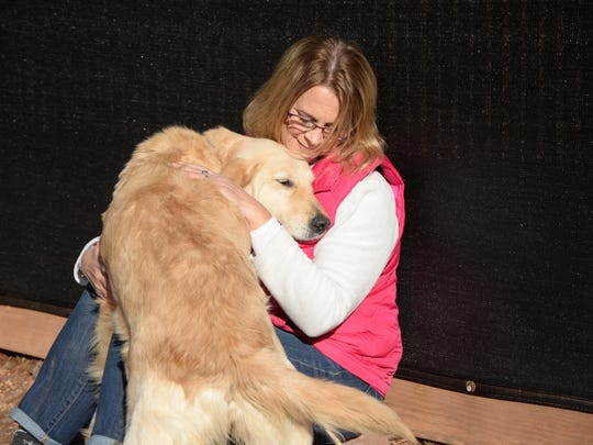 Inza Adams, development and donor engagement manager for the Delaware Valley Golden Retriever Rescue, plays with Mia — a golden retriever estimated to be less than two years old who was recently rescued from a South Korean meat farm.
