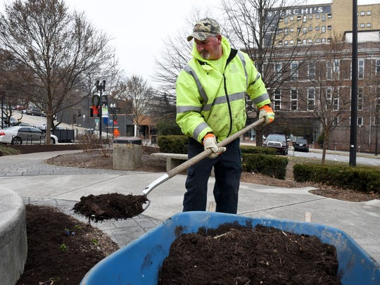 Knoxville horticulture worker Joe Collins deals with the below-freezing temperatures Wednesday, Jan. 3, 2018, while putting out mulch in downtown Knoxville.