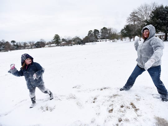 Savannah Stucker, left, and Loretta Compton throw snow