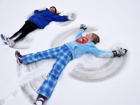 Anne Caroline Harris, 14, and Alexi Roth, 11, make snow angels after sledding at Gettysvue Country Club in West Knoxville on Tuesday, Jan. 16, 2018.