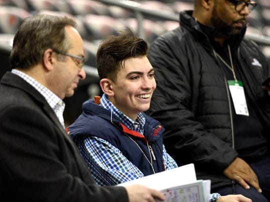 Jefferson High School senior Peter Fifoot, center, gets broadcasting pointers from NBC Sports Washington plaly-by-play announcer Joe Beninati, left, during the Washington Capitals' practice before facing the New Jersey Devils in Newark, New Jersey on Thursday, Jan. 18, 2018.