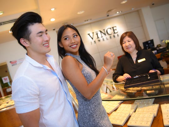 Models Diliana Tuncap and Sam Hashimoto is assisted by Store Manager Mila Bruan as they demonstrate the ease of shopping at Vince Jewelers in Hagåtña on Saturday, Jan. 20, 2018. Tuncap wears a sparkling 18-karat white gold halo design diamond ring with a 1.64 total carat weight paired with a platinum diamond bracelet embedded with 3.53 total carat weight in stones.