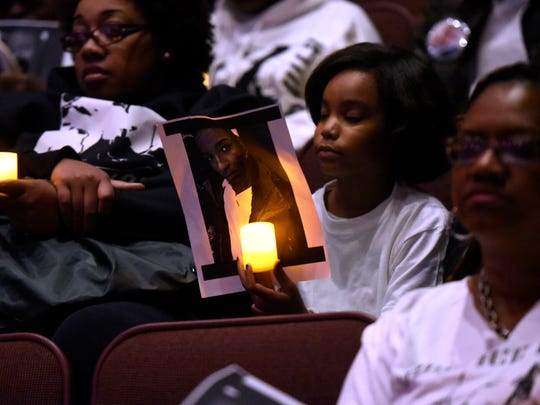 The family of Nadjhier Barner-Timmons holds photos of him during a candlelight vigil for crime victims in 2016.