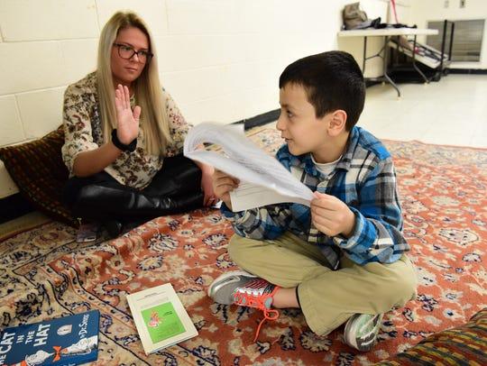 A volunteer, Olivia Shea, helps Nour Haj Hasan, 7,