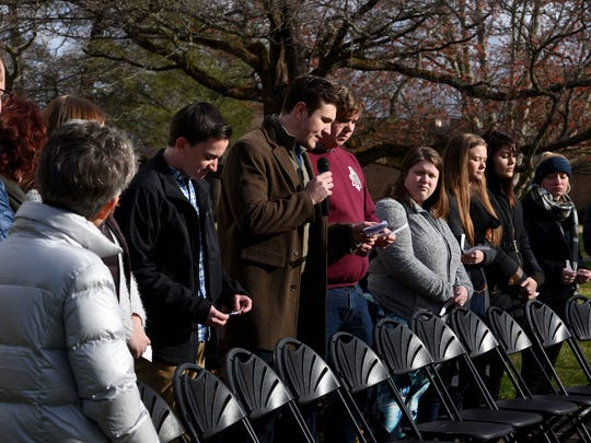 Maryville College student and event leader Jacob Williams, center with mic, reads the name and comments about one of the 17 killed in Florida recently as other strudents and staff participate in National School Walkout Wednesday, Mar. 14, 2018 in Maryville, Tenn.