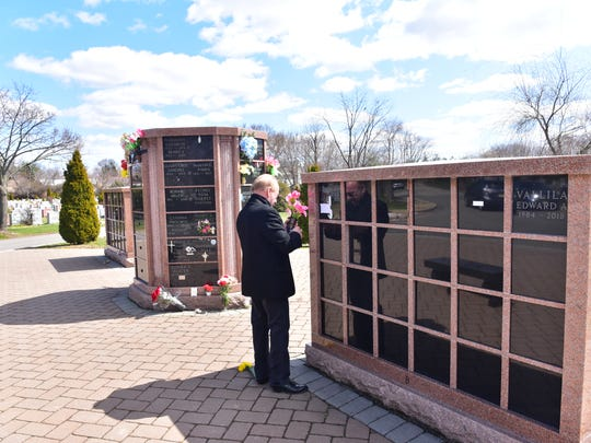 Gary A. Sciarrino, general manager/superintendent of East Ridgelawn Cemetery in Clifton, NJ, fixes a flower at the cemetery's outdoor columbarium.