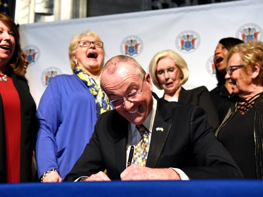 Former New Jersey Senator Diane Allen (second from left) laughs as Governor Phil Murphy (center) signs the Diane B. Allen Equal Pay Act in Trenton, NJ on Tuesday, April 24, 2018.