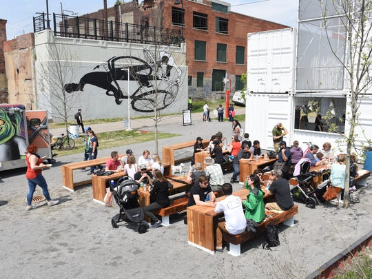 People enjoy family style seating and eat from food trucks at the Dequindre Cut Freight Yard as the Detroit Riverfront Conservancy celebrates the grand opening of the DCFY on Saturday May 19, 2018.