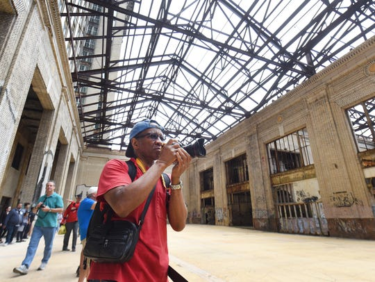 Photographer Ulysses Freeman of Detroit snaps hundreds of images of the concourse inside the Michigan Central Depot as Ford Motor Co. hosted tours of the station during an open house on Friday.
