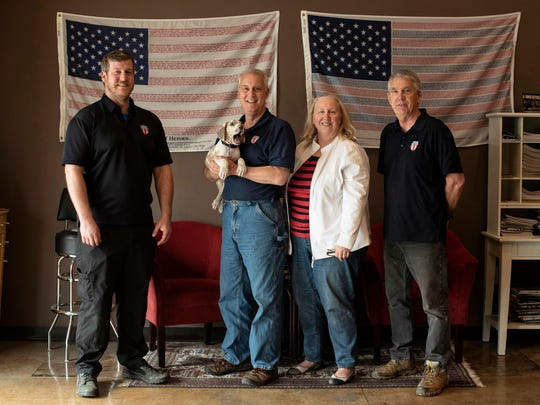 In this April 25, 2018, photo, the owners and employees of Honor Defense, a gunmaker in Gainesville, Ga., pose in the company's lobby. Standing, left to right, are Pete Ramey, who works on the assembly line, Gary Ramey, the company's owner, his wife and company business manager, Pam Ramey, and Richard Moore, who works on the assembly line.