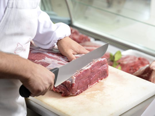 A meat cutter prepares to butcher a portion of meat for a customer.