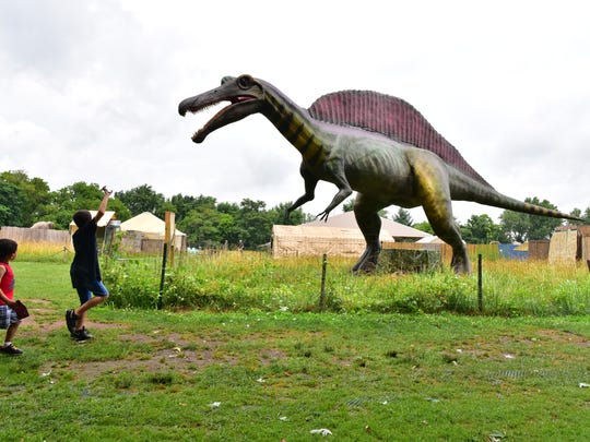 Brothers Lance 8, and Gavin Gailyard, 5, of Staten Island, NY, react to the sight of a Spinosaurus, the newest dinosaurs at Field Station in Leonia. The Spinosaurus was voted in by the children to be exhibited this season at Overpeck Park in Leonia and it is the largest Dinosaurs in the park.