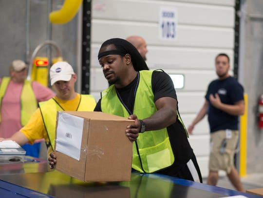Employee Arkeem Francois helps receive boxes that are