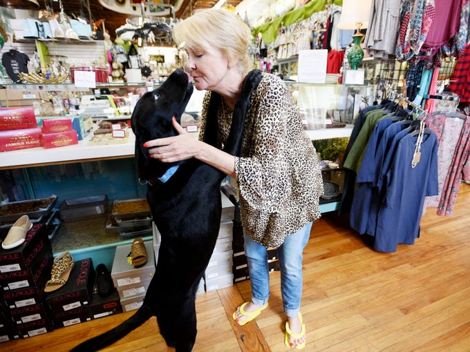 Darby's owner, Darby Short, pets her dog, Mary Francis,