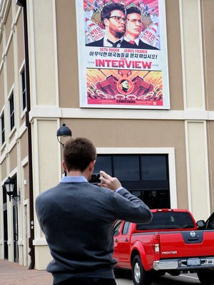 """A man uses his phone to take a photo of a large poster advertising the movie """"The Interview"""" on the back wall of the Alamo Drafthouse Cinema Tuesday, Dec. 23, 2014, in Houston. Sony Pictures Entertainment announced Tuesday a limited theatrical release of """"The Interview"""" beginning Thursday, putting back into the theaters the comedy that prompted an international incident with North Korea and outrage over its cancelled release. (AP Photo/Pat Sullivan)"""
