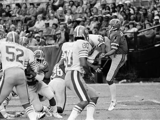 Falcons kicker Ralph Giacomarro, right, trying to punt