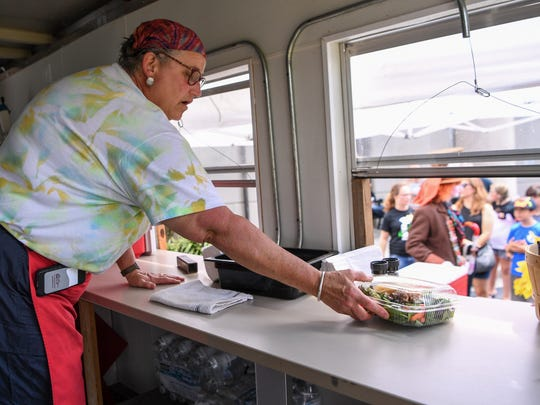 Katie Tillman sells a salad made with local grown vegetables from the Friend's food truck, during the Electric City Comic Con at the Anderson County Library on Saturday.