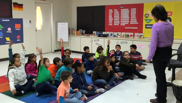 Students in a trilingual second-grade class raise their