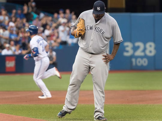 New York Yankees starting pitcher CC Sabathia, with the Blue Jays' Josh Donaldson circling the bases behind him, during a game in Toronto on Tuesday, Aug. 8, 2017. Sabathia only last three innings due to his aching right knee.