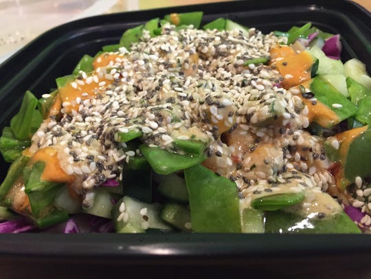 A chicken and rice bowl with veggies at Quarks American