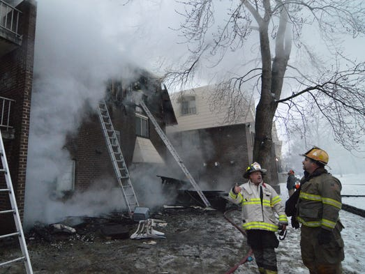 Firefighters work at a three-alarm fire at the Autumn