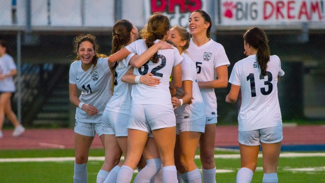 The St. Thomas More girls soccer team members congratulate one another after scoring their first goal as the Cougars take on the Destrahan Wildcats in a playoff game Friday Feb. 16, 2018.