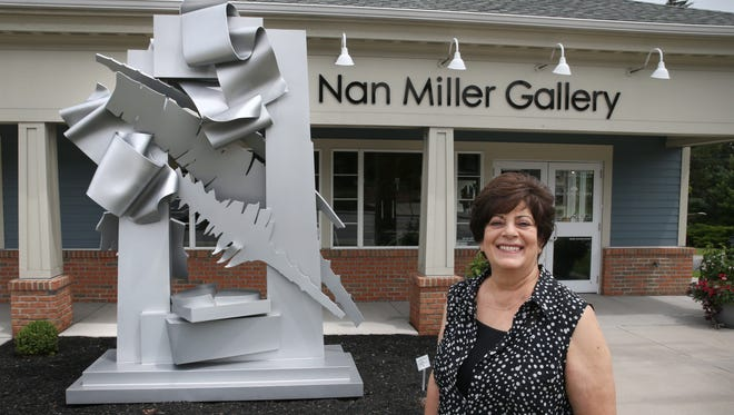 "Nan Miller at her well-known art gallery, the Nan Miller Gallery, on Monroe Avenue in Pittsford Friday, July 28, 2017.  At left is the gallery's signature piece, Albert Paley's stainless steel sculpture ""Proscenium."""