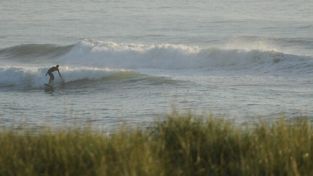 EASTHAM -- Surfers take to the waves off Coast Guard Beach Tuesday morning.