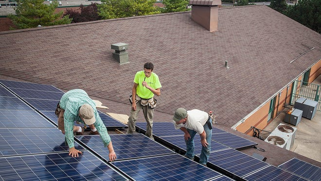 Workers with Indianapolis based company Rectify Solar LLC install solar panels on top of the Youth Opportunity Center on Kilgore Avenue Wednesday Oct. 7, 2015.