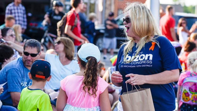Democratic congressional candidate Kimberly Bizon hands out candy during the Rotary International Day Parade, Bizon Tuesday's primary and will face the incumbent, Paul Mitchell, in November.