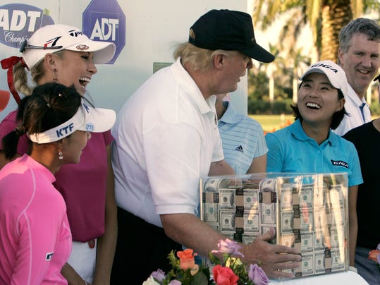 FILE - This Nov. 18, 2006 file photo shows Donald Trump, center, putting his hands on a box of money while posing for a photo with the eight golfers who qualified for the final round following the third round of the LPGA ADT Championship at the Trump International Golf Club in West Palm Beach, Fla. Also present, from left to right, are: Mi Hyun Kim, of South Korea, Natalie Gulbis and il Mi Chung, also of South Korea. The U.S. Women's Open will be played next week at a golf course in New Jersey owned by President Trump. The USGA awarded the site in 2012 and later came under pressure from women's groups and three Democratic U.S. senators to move the event because of Trump's comments about women and minorities. It's uncertain if the president will attend the tournament in Bedminster, New Jersey. (AP Photo/Lynne Sladky)