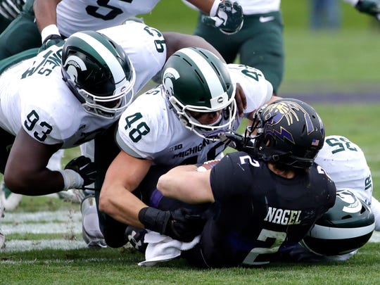 Kenny Willekes (48), Naquan Jones (93) and Joe Bachie (35) tackle Northwestern's Flynn Angel on Oct. 28, 2017 in Evanston, Ill.