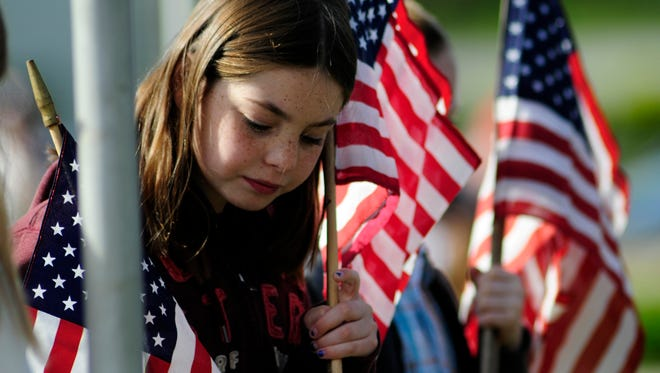 A young girl places a flag during a Prospect Hill Cemetery Afghanistan Flag Memorial event. John A. Pavoncello photo