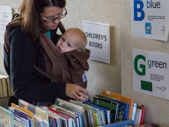 A woman and child peruse books during the Lester Library's
